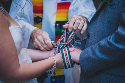 Celtic priest tying a knot around a couple's hands for a Celtic handfasting ceremony