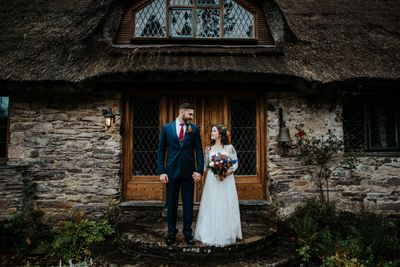 Couple eloping in Ireland in front of a thatched roof cottage