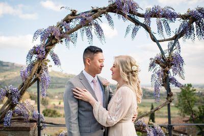 Intimate Italian wedding ceremony under a wisteria arch