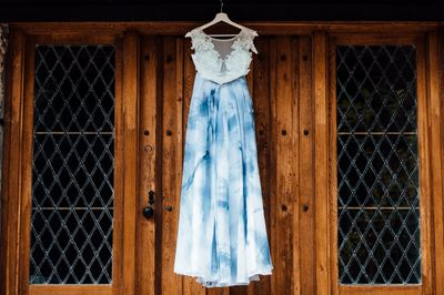 Blue tie-dye wedding dress hung from a rustic cottage door